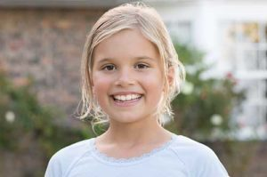 young girl smiling after pediatric dentistry in TX